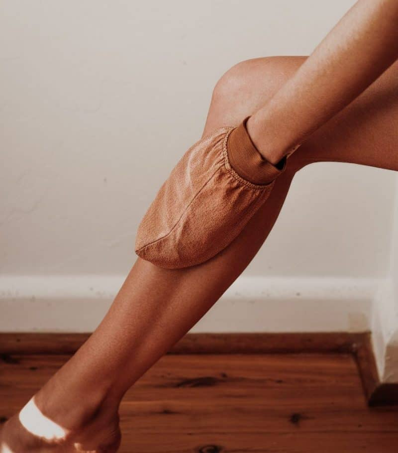 Woman using brown exfoliating mitt on tanned leg