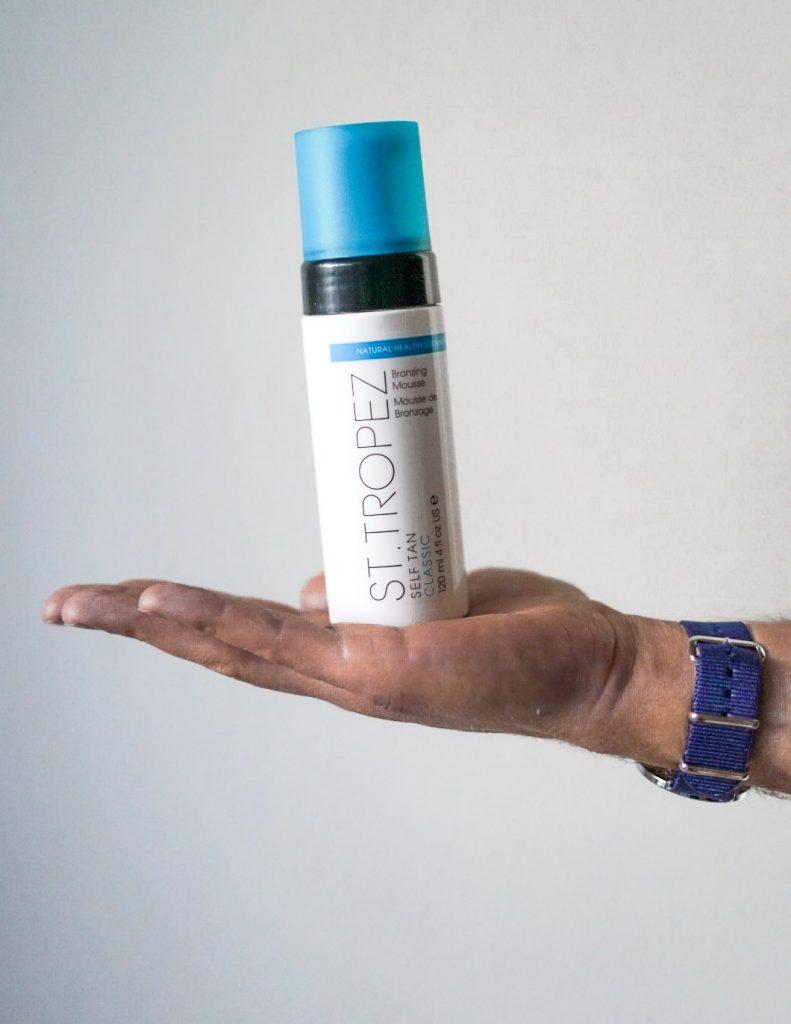 man holding St. Tropez fake tan bottle