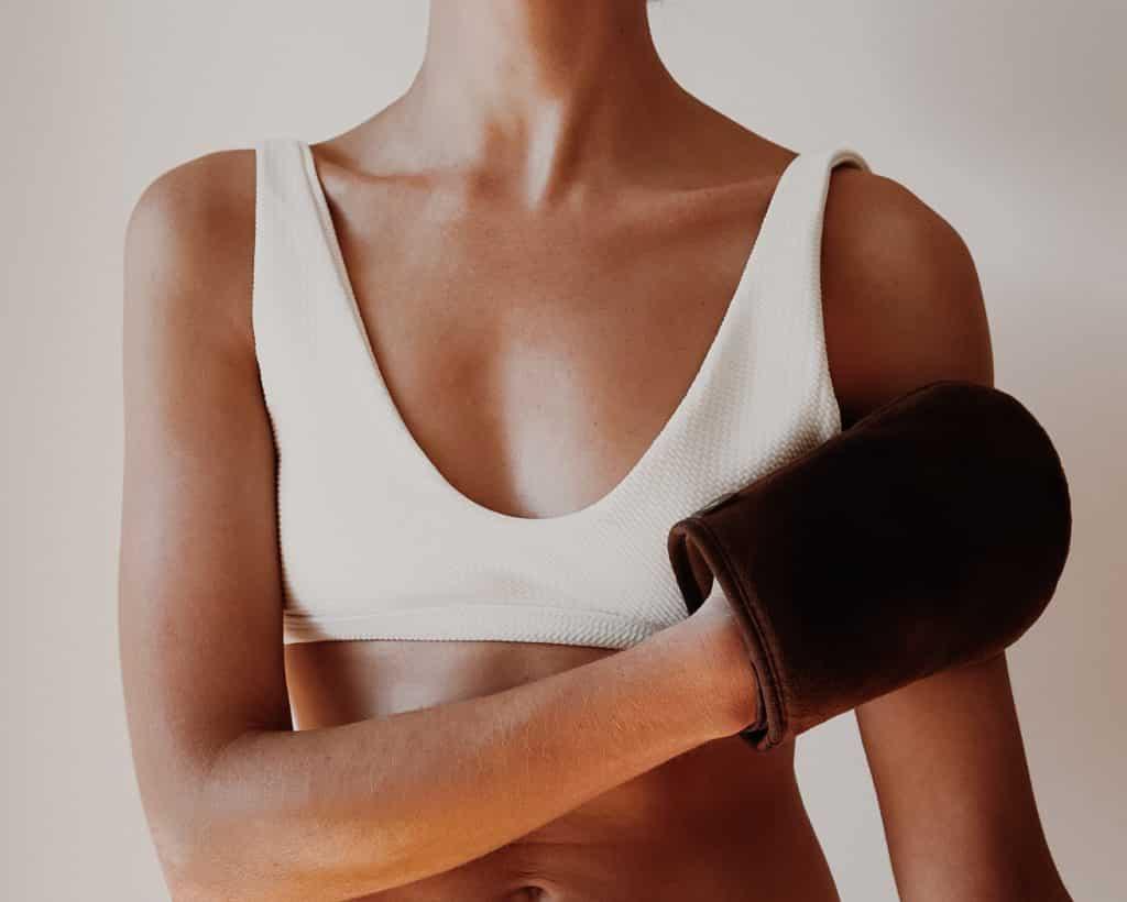 woman applying fake tan to body